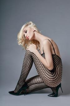 Blond kobieta w body z idealnym ciałem siedzącym na podłodze.