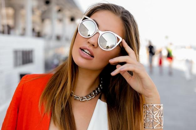 Blond kobieta w dużych okularach przeciwsłonecznych z pełnymi ustami, pozowanie na świeżym powietrzu. czerwona kurtka, stylowe srebrne dodatki.