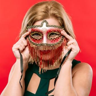 Blond kobieta w jaskrawej karnawał masce