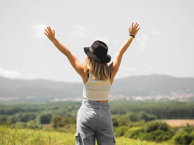 Blond kobieta w kapeluszu z podniesionymi rękami