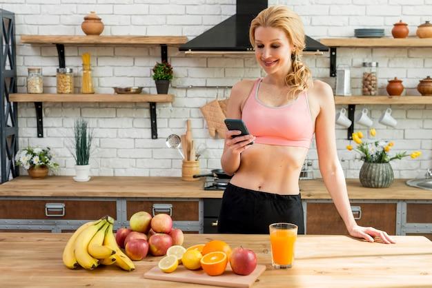 Blond kobieta w kuchni z owoc