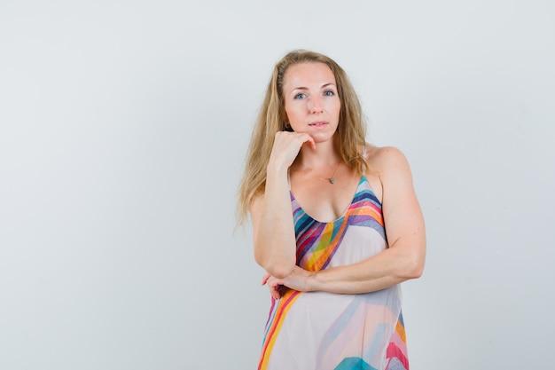 Blond kobieta w letniej sukience stojącej w myśleniu poza i patrząc zniewalająco