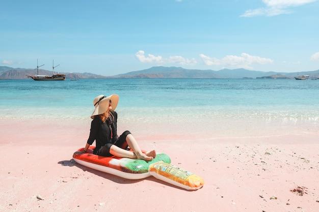 Blond kobieta w letnim kapeluszu i okularach przeciwsłonecznych relaksuje się na dmuchanym materacu w różowej piaszczystej plaży
