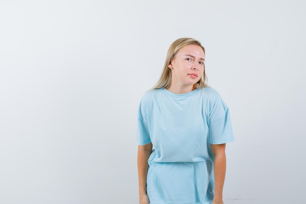 Blond kobieta w niebieskiej koszulce stojąca prosto i pozująca do kamery i wyglądająca uroczo