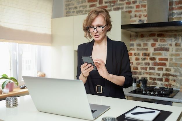 Blond kobieta w okularach pracuje zdalnie w swojej kuchni. poważna dziewczyna spokojnie przegląda wiadomości w internecie ze swoim smartfonem w domu.