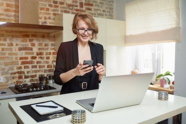 Blond kobieta w okularach pracuje zdalnie w swojej kuchni. szczęśliwa dziewczyna z aparatami ortodontycznymi przegląda wiadomości w internecie za pomocą smartfona w domu.