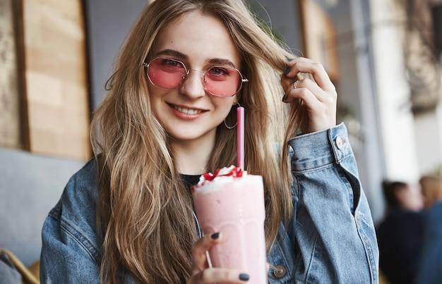 Blond kobieta w okularach przeciwsłonecznych pije koktajl truskawkowy w kawiarni