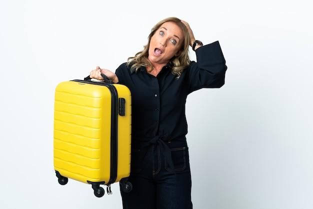 Blond kobieta w średnim wieku na odosobnionym białym tle na wakacjach z walizką podróżną i zdziwioną