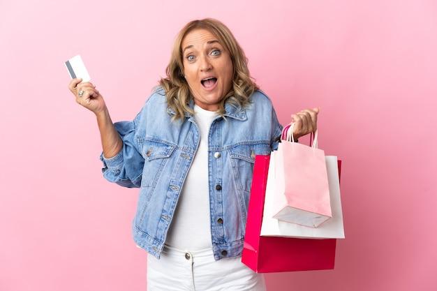 Blond kobieta w średnim wieku na różowym tle trzyma torby na zakupy i jest zaskoczona