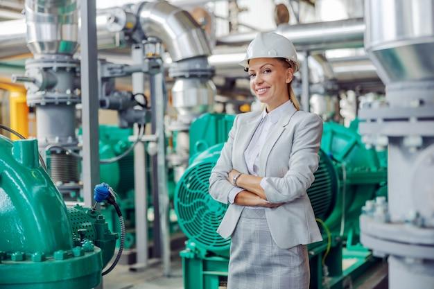 Blond kobieta w średnim wieku, odnosząca sukcesy dyrektor generalna w garniturze z hełmem na głowie, stojąca w elektrowni ze skrzyżowanymi rękami
