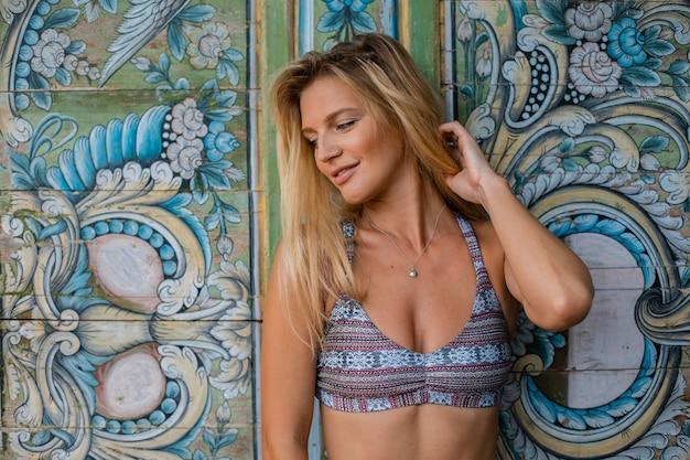 Blond kobieta w strojach kąpielowych, pozowanie za ścianą