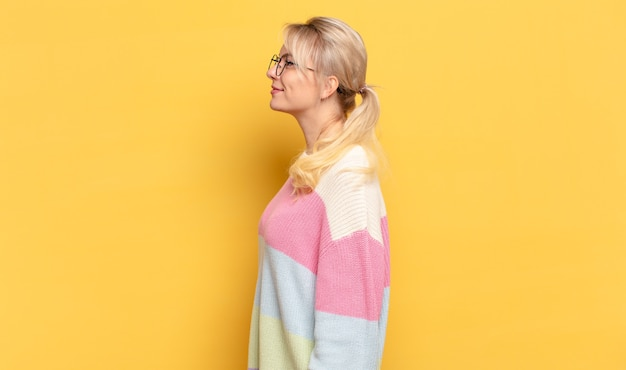 Blond kobieta w widoku profilu, chcąc skopiować przestrzeń do przodu, myśląc, wyobrażając sobie lub marząc na jawie
