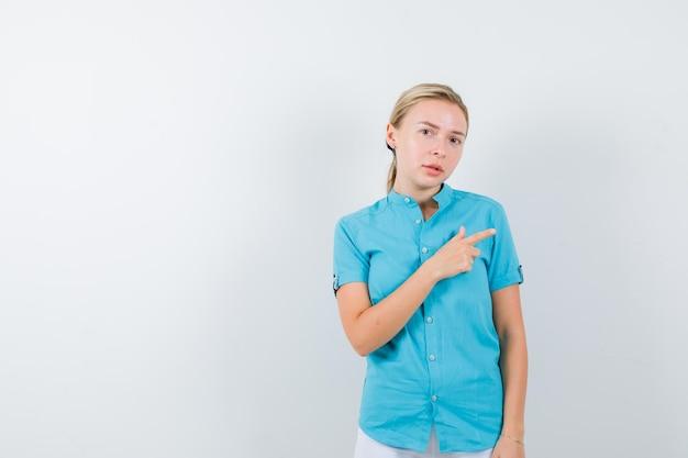 Blond kobieta wskazująca w prawo w niebieskiej bluzce i wyglądająca poważnie na białym tle