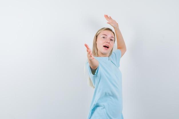 Blond kobieta wskazuje palcami wskazującymi w niebieskiej koszulce i wygląda na szczęśliwą