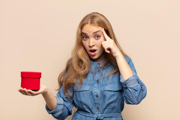Blond kobieta wygląda na zaskoczoną, z otwartymi ustami, zszokowaną, realizując nową myśl, pomysł lub koncepcję