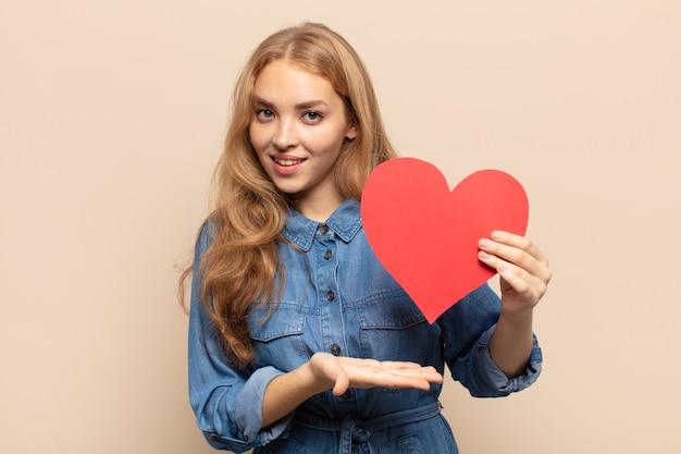 Blond kobieta wyglądająca na zaskoczoną i zszokowaną, z opuszczoną szczęką, trzymająca przedmiot z otwartą dłonią z boku