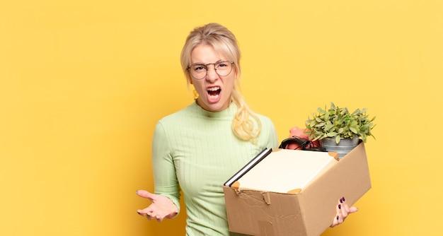 Blond kobieta wyglądająca na złą, zirytowaną i sfrustrowaną krzyczącą wtf