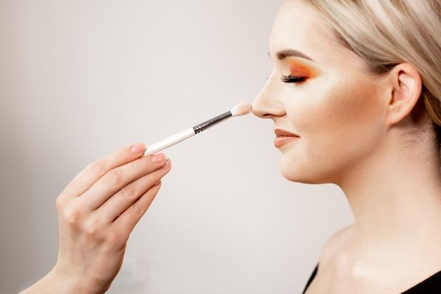 Blond kobieta z jasny makijaż w profilu. w ramce ręka charakteryzatora trzyma pędzel do makijażu. model blondynka uśmiecha się