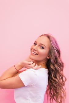 Blond kobieta z kręconymi pięknymi włosami, uśmiechając się na białym tle