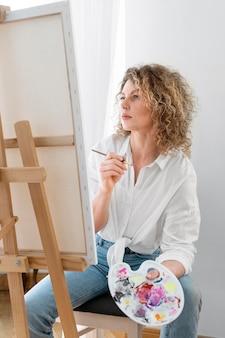 Blond kobieta z kręconymi włosami maluje w domu