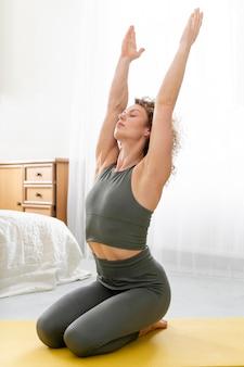 Blond kobieta z kręconymi włosami robi joga w domu