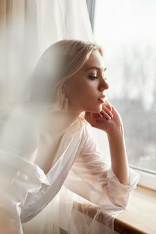Blond kobiety z kolczykami w uszach w promieniach wieczornego słońca.