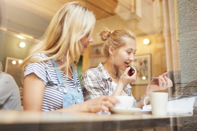 Blond koleżanki siedzi w kawiarni