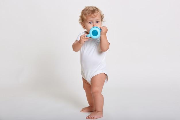 Blond kręcone dziecko pije wodę z butelki, patrzy prosto w kamerę, ubrane w body