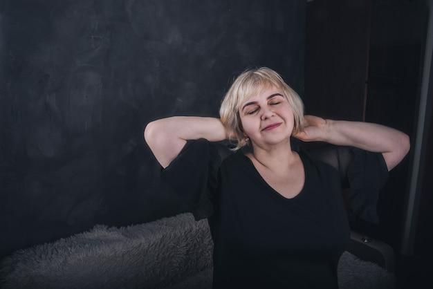Blond, krótkowłosa, pulchna starsza kobieta w czarnym ubraniu na solidnym tle z ciemnoszarego betonu.