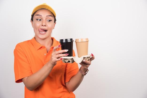 Blond kurierka trzyma dwie filiżanki kawy na białej ścianie.