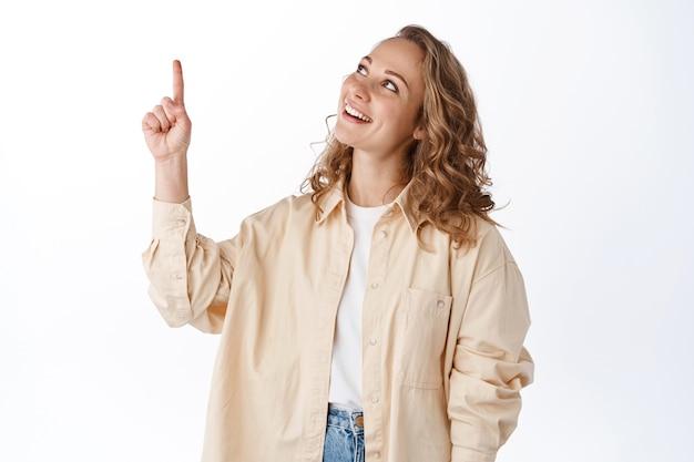 Blond ładna dziewczyna wskazująca i patrząca na tekst promocyjny, pokazujący baner, stojący nad białą ścianą