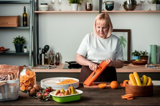Blond ładna gospodyni stoi przy kuchennym stole i kroi świeże pomarańcze wśród misek z kiwi, truskawkami, gruszkami i bananami