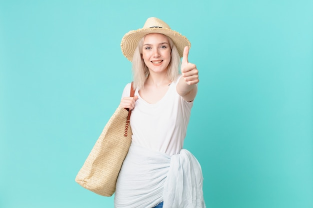 Blond ładna kobieta czuje się dumna, uśmiechając się pozytywnie z aprobatami. koncepcja lato
