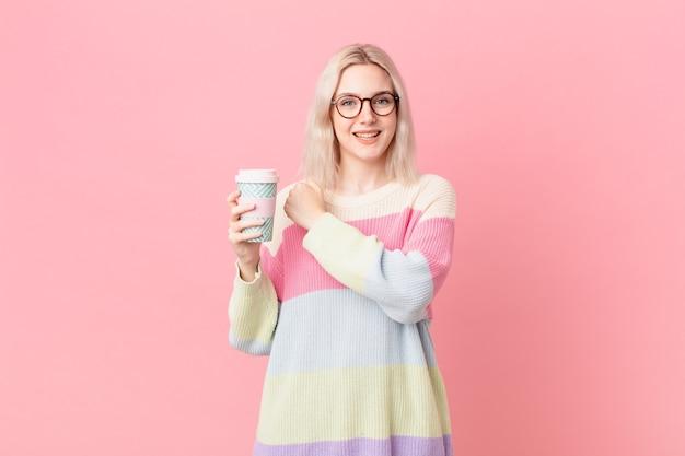 Blond ładna kobieta czuje się szczęśliwa i stoi przed wyzwaniem lub świętuje. koncepcja kawy