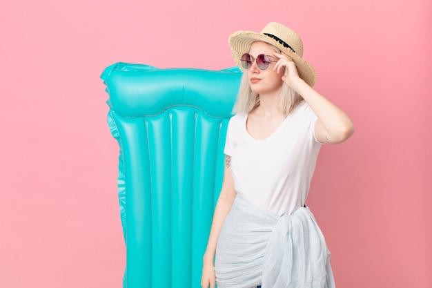 Blond ładna kobieta czuje się zakłopotana i zdezorientowana, drapiąc się po głowie. koncepcja lato