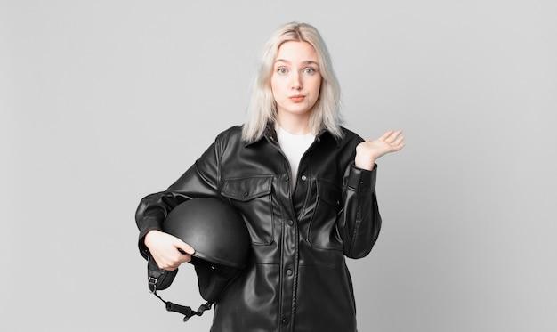 Blond ładna kobieta czuje się zakłopotana, zdezorientowana i wątpi. koncepcja motocyklisty