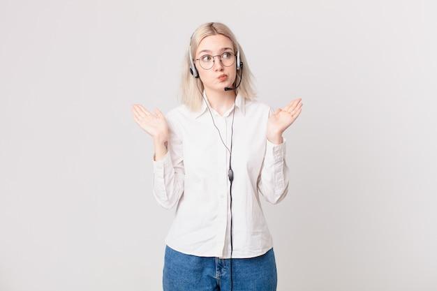 Blond ładna kobieta czuje się zdziwiona, zdezorientowana i wątpi w koncepcję telemarketingu