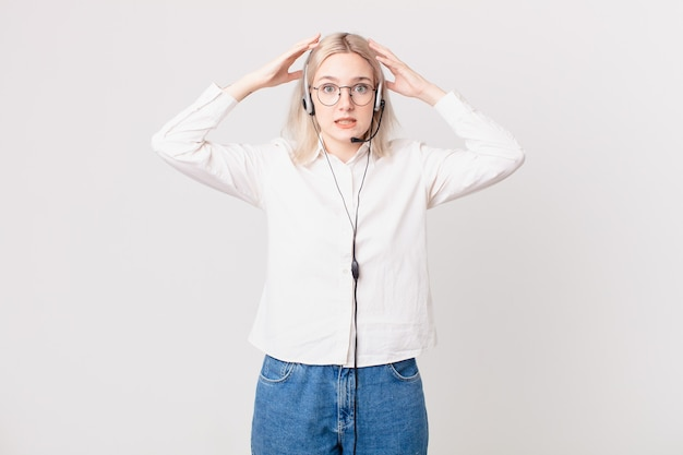 Blond ładna kobieta czuje się zestresowana, niespokojna lub przestraszona, z rękami na głowie koncepcja telemarketingu
