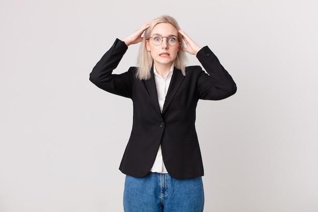Blond ładna kobieta czuje się zestresowana, niespokojna lub przestraszona, z rękami na głowie. pomysł na biznes