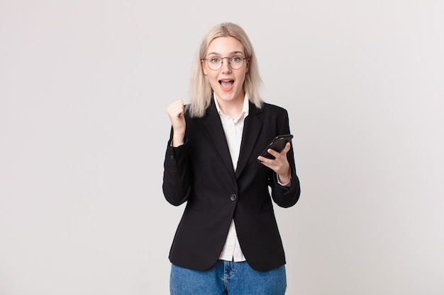Blond ładna kobieta czuje się zszokowana, śmieje się i świętuje sukces i trzyma telefon komórkowy