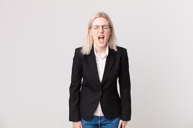 Blond ładna kobieta krzyczy agresywnie, wyglądając na bardzo rozgniewaną. pomysł na biznes