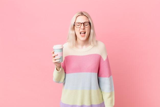 Blond ładna kobieta krzyczy agresywnie, wyglądając na bardzo złą. koncepcja kawy