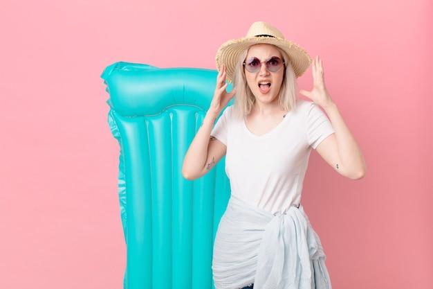 Blond ładna kobieta krzyczy z rękami w powietrzu. koncepcja lato