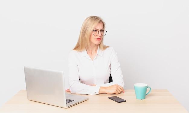 Blond ładna kobieta młoda blondynka czuje się smutna, zdenerwowana lub zła, patrzy w bok i pracuje z laptopem