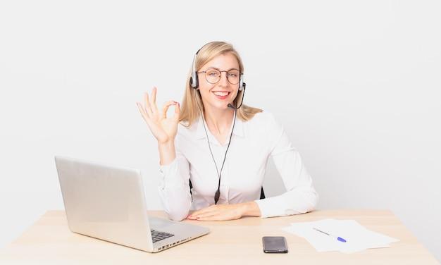 Blond ładna kobieta młoda blondynka czuje się szczęśliwa, pokazując aprobatę dobrym gestem i pracując z laptopem