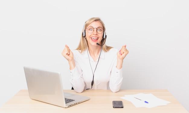 Blond ładna kobieta młoda blondynka czuje się w szoku, śmieje się i świętuje sukces i pracuje z laptopem