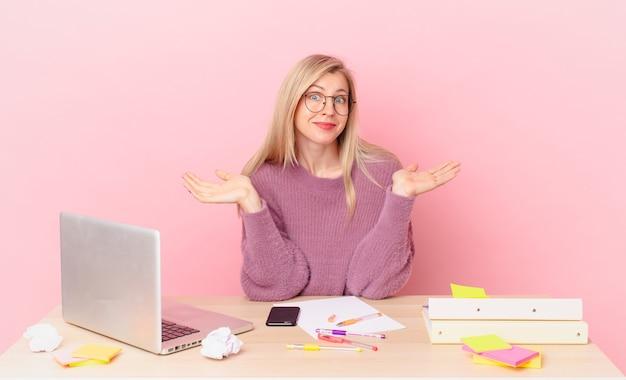 Blond ładna kobieta młoda blondynka czuje się zakłopotana i zdezorientowana, wątpi i pracuje z laptopem