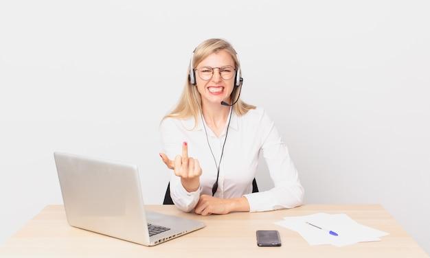 Blond ładna kobieta młoda blondynka czuje się zła, zirytowana, buntownicza i agresywna i pracuje z laptopem