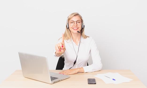 Blond ładna kobieta młoda blondynka uśmiecha się dumnie i pewnie robi numer jeden i pracuje z laptopem