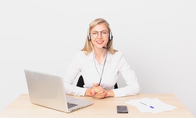 Blond ładna kobieta młoda blondynka uśmiecha się radośnie z ręką na biodrze i pewnie pracuje z laptopem